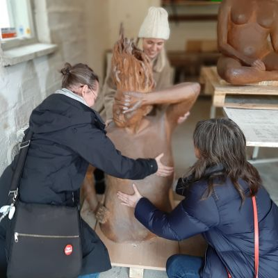 Tre damer vänder på en stor och tung keramikskulptur, föreställande överkroppen av en naken dam med böljande hår.