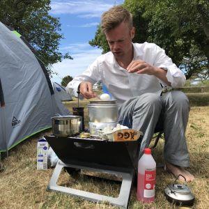 En man i vit skjorta kokar ägg på ett spritkök utanför sitt tält.