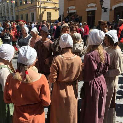 Folk står i en samling under medeltida marknaden i Åbo.