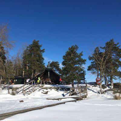 Karhusaaren laavu aurinkoisena talvipäivänä Saimaan jäältä kuvattuna