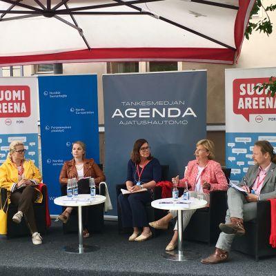 Nicke Lingnell (moderator), Miapetra Kumpula-Natri, Katri Kulmuni, Britt Lundberg, Anna-Maja Henriksson och Juho Eerola sitter bredvid varandra. Henriksson talar.
