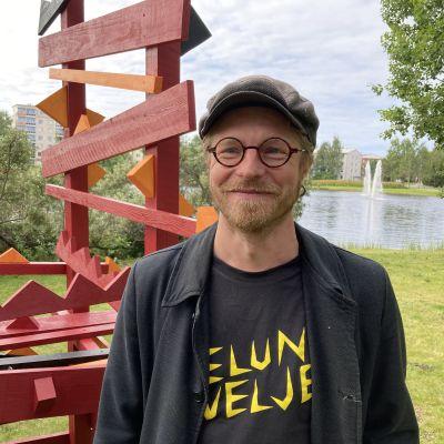Kuvataiteilija Tuomas Korkalo seisoo ympäristötaideteoksen vieressä. Taustalla on Rovaniemen Kirkkolampi.