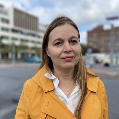 Keltatakkinen nainen Tampereen hallintorakennus taustalla.
