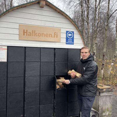 Valto Vaaraniemi seisoo polttopuuautomaatin edessä ja ottaa halkoja automaatista.