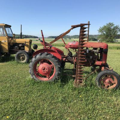 Kaksi vanhaa traktoria pellolla.