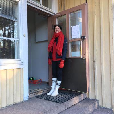 Nainen pitää vanhan kyläkoulun ovea auki nojaamalla siihen.