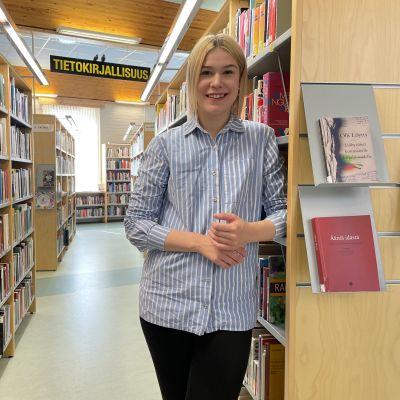 Suomussalmen uusi kunnanvaltuutettu Milla Veteläinen seisoo kirjaston hyllyjen välissä ja katsoo hymyillen suoraan kameraan.