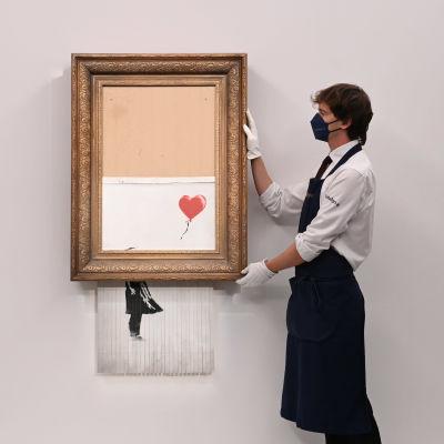 En man håller i tavlan Love is in the bin, dvs en målning med en flicka och en ballong som är halft sönderstrimlad i sin ram.