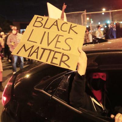 Bild på arm som håller ut skylt där det står att svarta liv är värda lika mycket ur en bil.