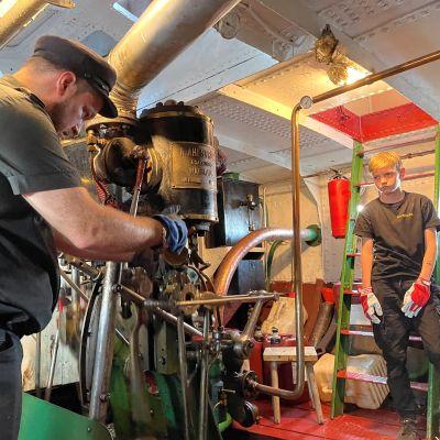 S/S Koutan konemestari Ari Pihlajaniemi huoltaa höyrylaivan koneistoa ja hänen poikansa seuraa sivusta.