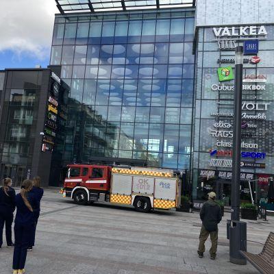 Paloauto ja ihmisiä oululaisen kauppakeskus Valkean ulko-ovien edessä.