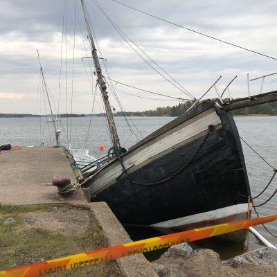 En stor båt med mast, kanske trålare som håller på att sjunka i vatten, nära strand.