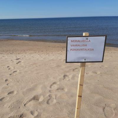 Virtauksista varoittava kyltti hiekkarannalla.