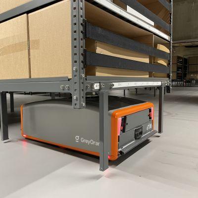 Matala oranssi-harmaa robotti, jonka päällä on hyllykkö.