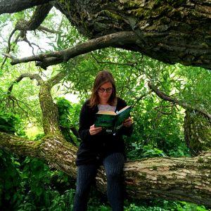 Kaisa Pulakka istuu puussa ja lukee Ronja, ryövärintytärtä