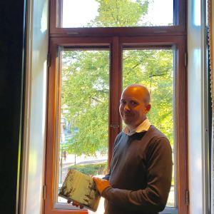 Samu Nyström står vid ett fönster som vetter mot Esplanadparken.