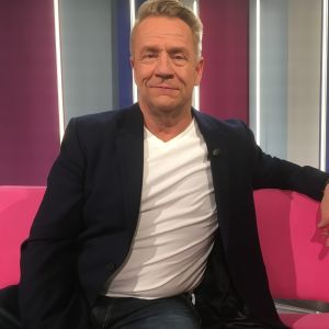 Olli Lindholm istuu Puoli seitsemän ohjelman sohvalla studiossa.