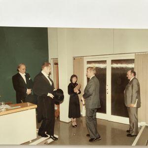 Kaisa Häkkisen väitöstilaisuus Turun yliopistossa helmikuussa 1984. Vasemmalla professori Mikko Korhonen, seuraavana professori Alho Alhoniemi, Kaisa Häkkisen oikealla puolella professori Osmo Ikola ja äärimmäisenä oikealla professori Kalevi Wiik.
