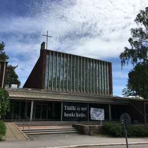 """Remontissa oleva Herttoniemen kirkko. Edustalla lakana """"Täällä ei nyt henki kulje""""."""