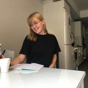 Otnäsbon Wilma Branders sitter vid sitt matbord med en kaffekopp framför sig och en penna i handen. Hon ler.