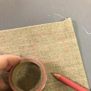 Käsi pitää teippirullan, piirrettu ympyrä kankaalla ja tekstiilikynä kankaalla