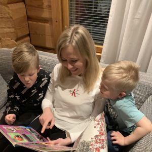Äiti lukee kirjaa kahdelle pojalleen sohvalla.