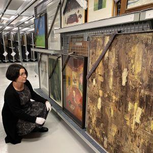 Kokoelmapäällikkö Sari Kainulainen katselee kokoelmaan kuuluvia maalauksia