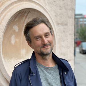 En leende mörkhårig man vid en husvägg.