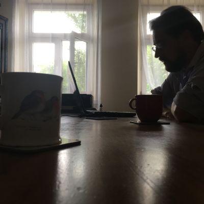 Anthony Goltz sitter i mörkret vid sin bärbara dator med ljusa fönster i bakgrunden