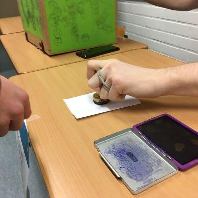 En hand stämplar en valsedel