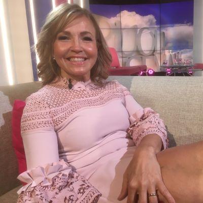Marita Taavitsainen istuu mukavasti Puoli seiskan studiossa sohvalla.