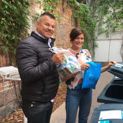 Skådespelaren Jarmo Mäkinen och projektledaren Anna von Zweygbergk från Håll skärgården ren står vid en skräpkontainer och ska slänga in varsin påse med skräp.