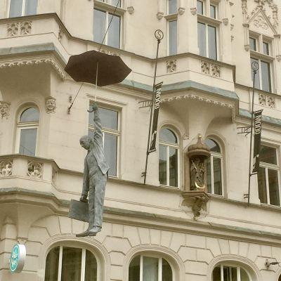 En staty i Prag av en man med paraply som hänger i luften över gatuhöjd.