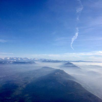 De franska och schweiziska Alperna täcks delvis av moln och atmosfären ovanför ser kylig ut i solskenet.