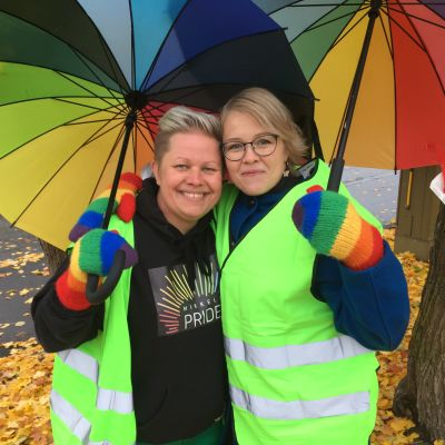 Kaksi naista seisoo puun alla sateenkaarilapaset käsissään.