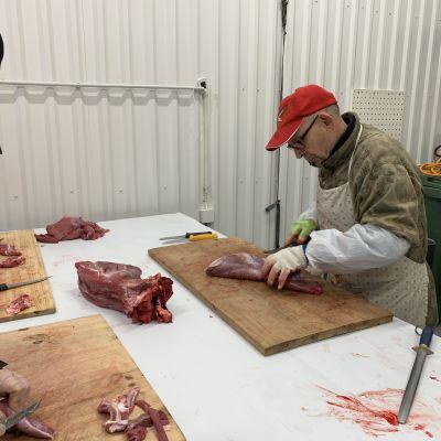Lihanleikkaaja Esko Puumalainen näyttää Kainuun ammattiopiston kokkiopiskelijoille mallia, kuinka hirvenlihaa leikataan.