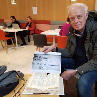 En man sitter och håller upp ett papper.