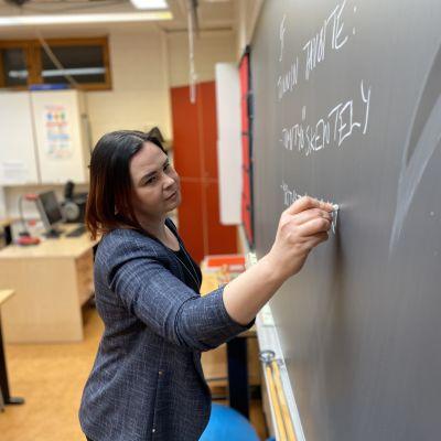 Opettaja Riina Mäkelälammi kirjoittaa taululle