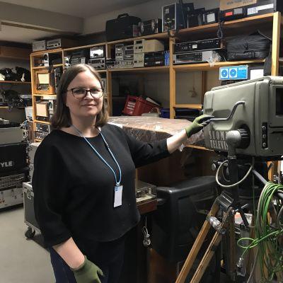 Silmälasipäinen nainen seisoo teknisiä laitteita sisältävien hyllyjen edessä ja pitää hansikoidulla kädellä kiinni vanhasta jaloilla seisovasta tv-kamerasta, jossa lukee Suomen Televisio.