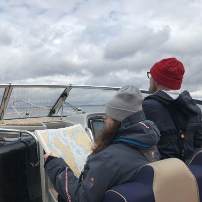 Nainen lukee karttaa veneessä, jota mies ohjaa Vesijärvellä.