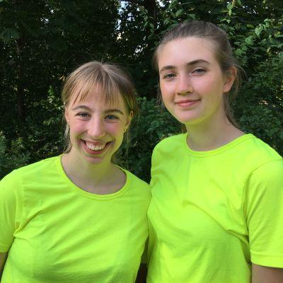 Två unga kvinnor ler in i kameran. I bakgrunden grönskar en trädgård.