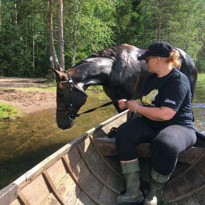 Nainen istuu veneessä, hevonen kahlaa vedessä veneen vieressä