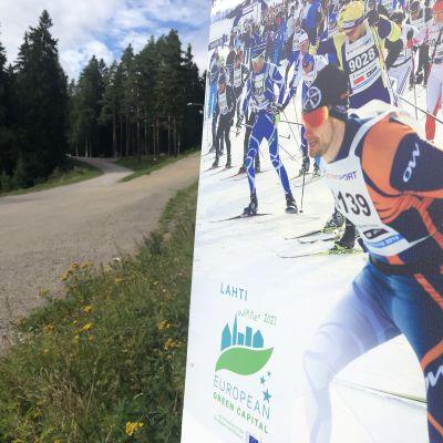 Finlandia-hiihdon mainoskyltti Lahden urheilukeskuksen maastossa kesällä 2020.