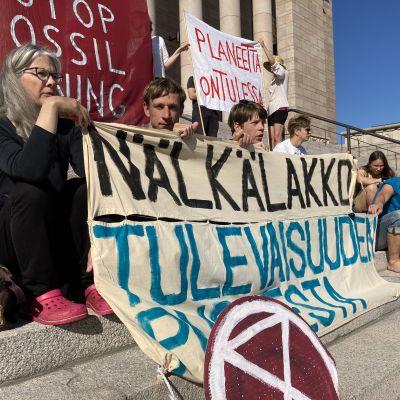 Kuva Elokapina-liikkeen syömälakkoon osallistuneista Eduskuntatalon edustalla.