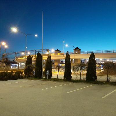 Asfalterade parkeringsplatser och gröna buskar framför en vit bro nattetid.