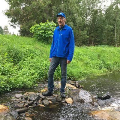 Siikaputaan tulvauomalla kyläyhdistyksestä kunnostetun uoman rannalla hankkeen puuhamies Pentti Haapakangas.