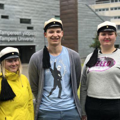 Kolme tupsulakkista teekkariopiskelijaa Tampereen yliopiston edessä.