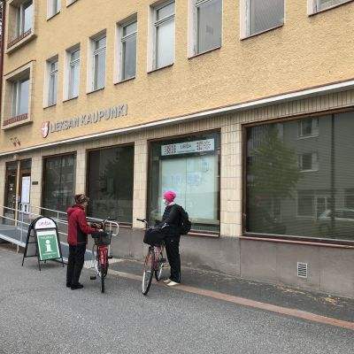 Kaksi naista polkupyörineen Lieksan keskustan raitilla.