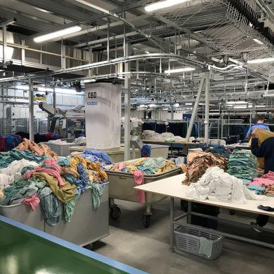 Työntekijä viikkaa potilasvaatteita Sakupen sairaalapesulassa Joensuussa.
