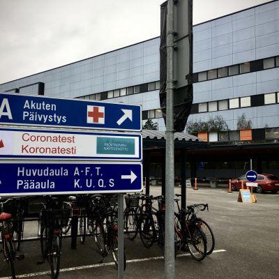 Koronatestauskyltti sairaalan päivystyksen ulkopuolella.